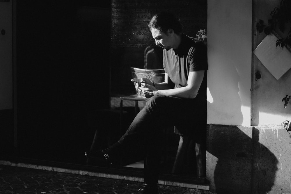 grayscale photography of man sitting beside table