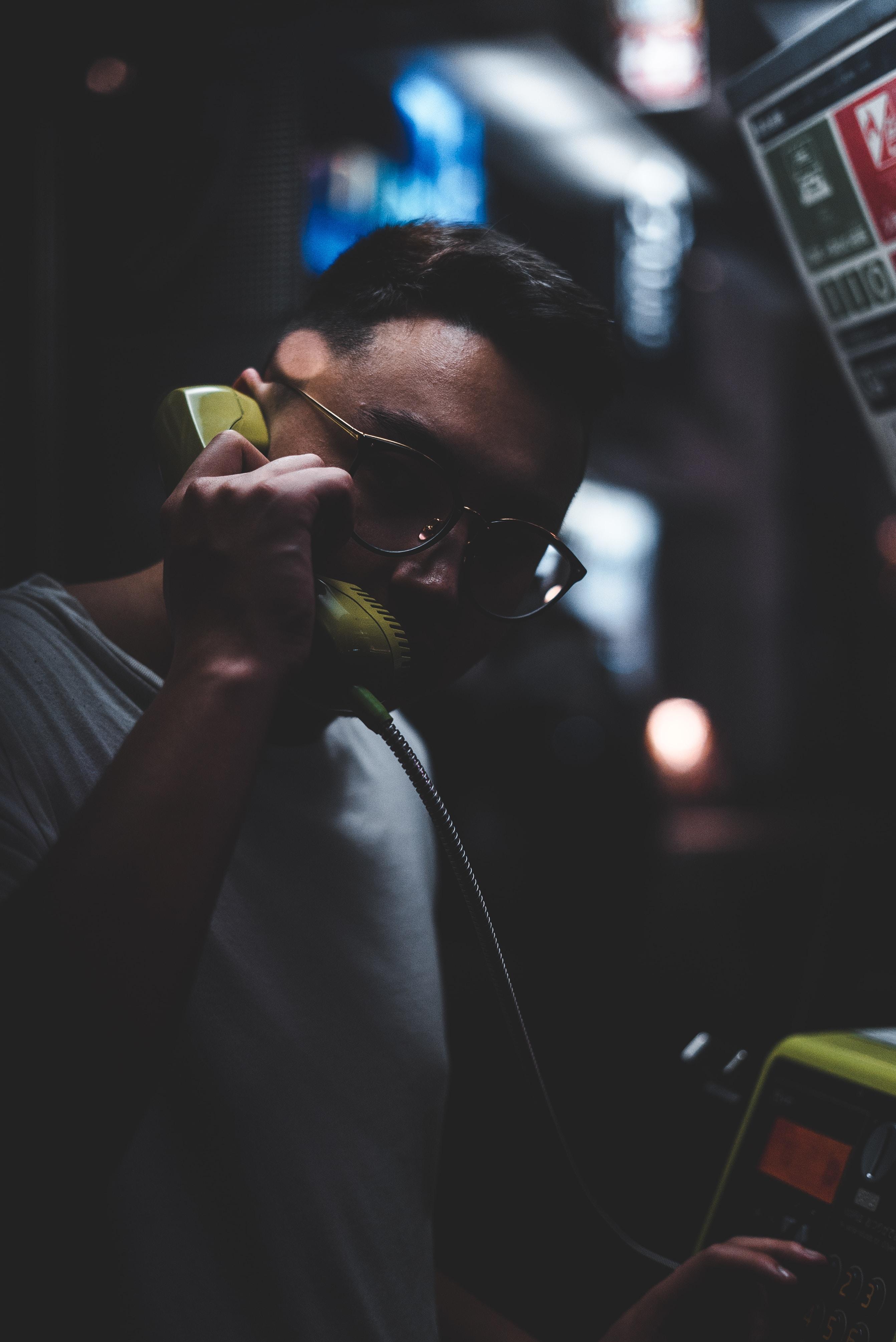 man standing holding telephone