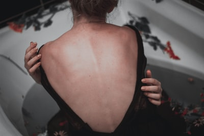 Girl holding herself with hands nacked back