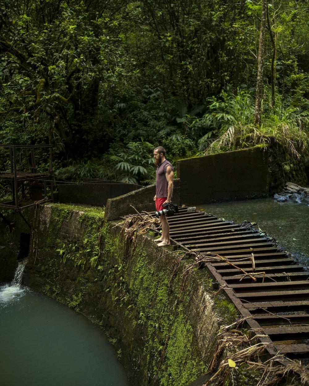 man standing on divider rock near waterfalls