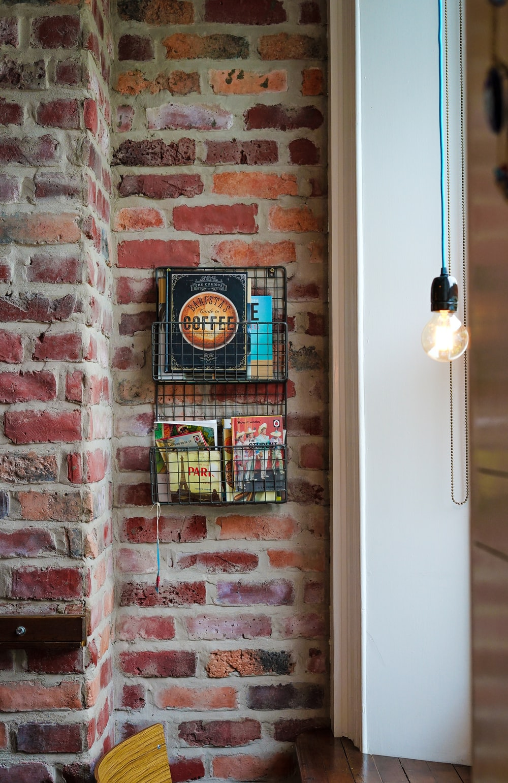 assorted magazines on gray metal wall rack