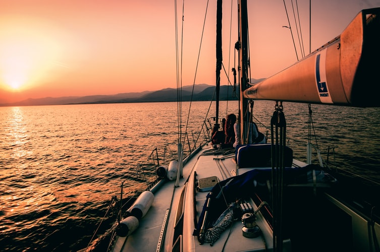 sustainable travel - sailing in sunset white boat