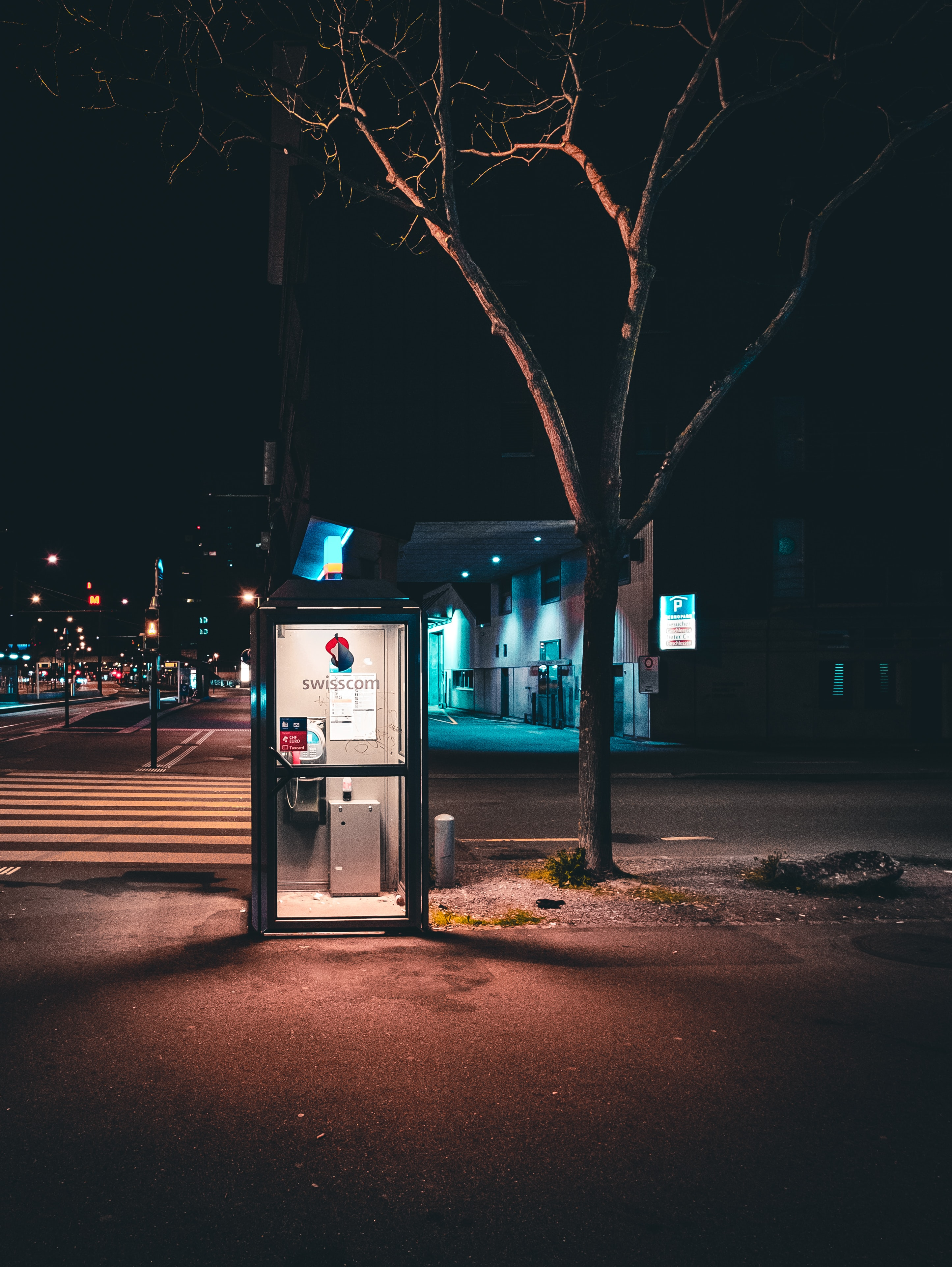 black lighted telephone booth near tree at nighttime photography