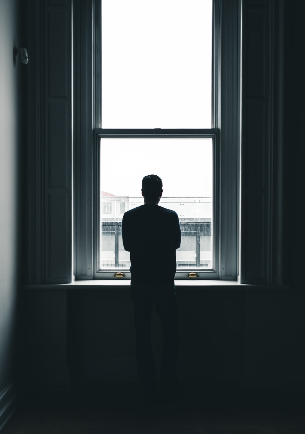 silhouette of person standing in front of window at daytime