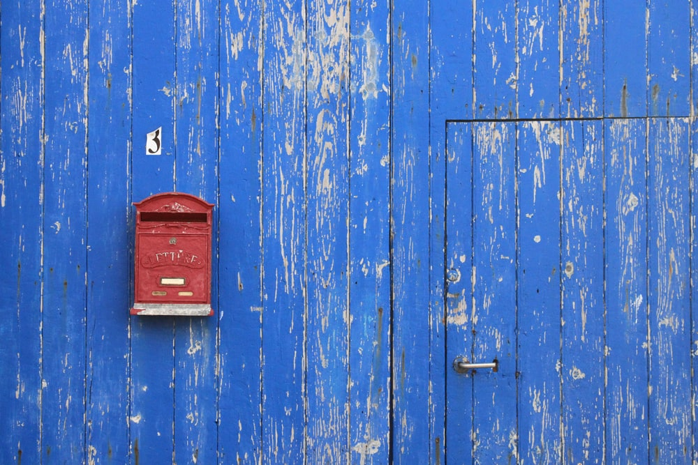 red metal mailbox on blue wooden wall