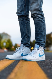 selective focus photography of person wearing blue-and-white Nike Air Jordan 1's