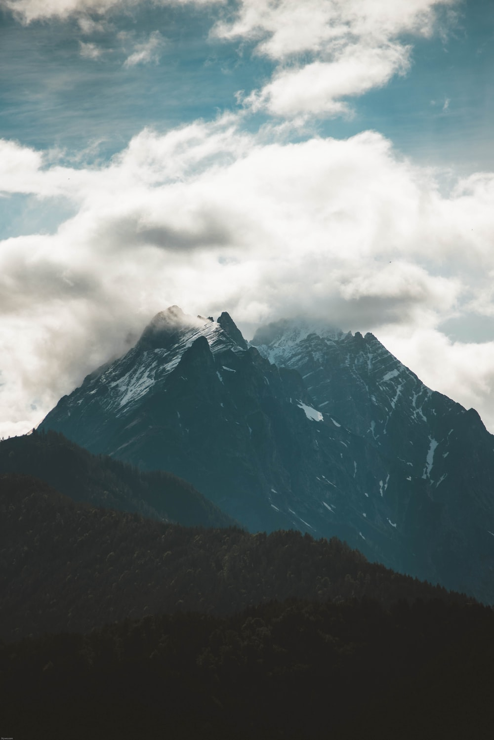 peak of mountain covered by clouds