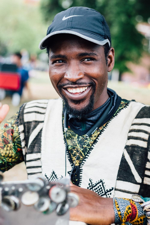 smiling man wearing black Nike baseball cap
