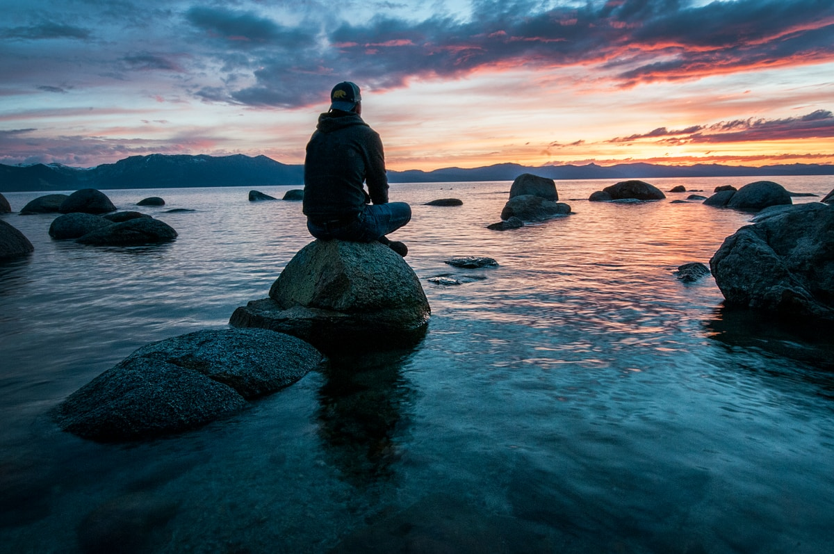 A seated person wearing a backwards baseball cap, hoodie, and jeans sitting cross-legged on a rock surrounded by water and other rocks watching a sunrise or sunset.
