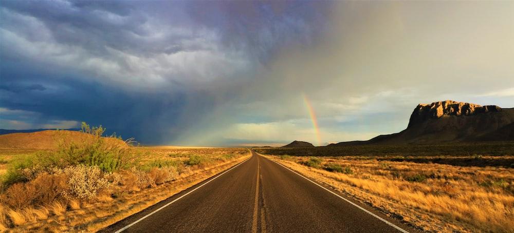 road between open field near mountain