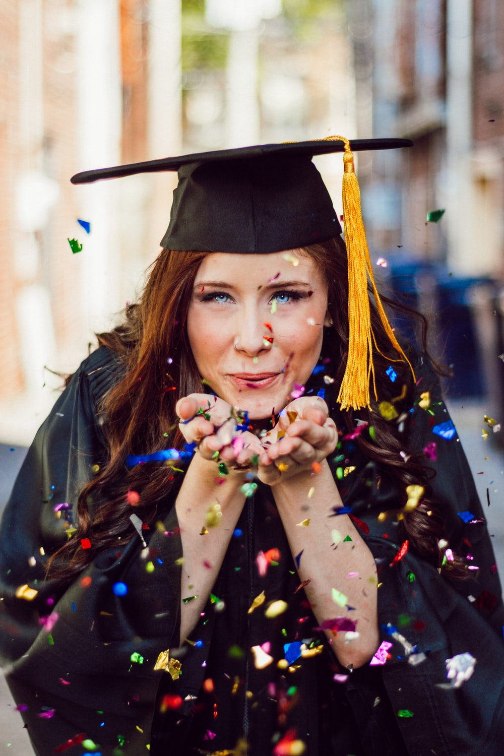woman blowing assorted color confettis