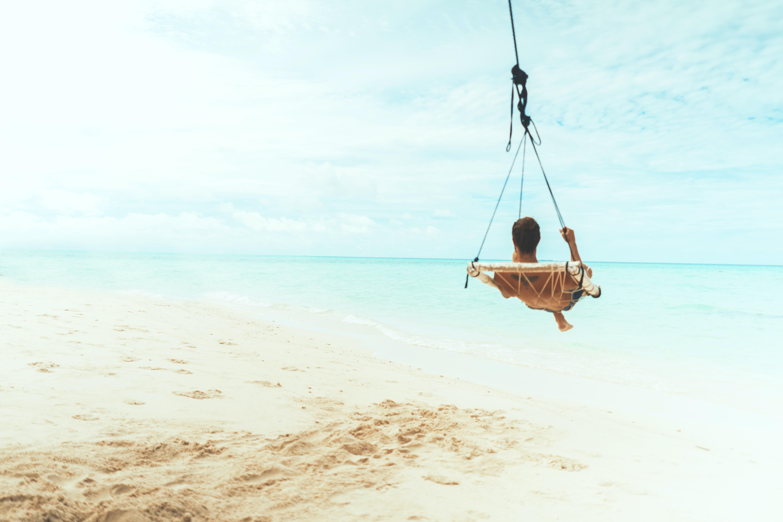 man swing beside body of water