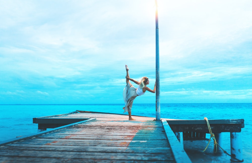 woman stretching on wooden dock while holding post by the sea during daytime