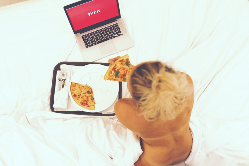 woman sitting on bed while eating pizza