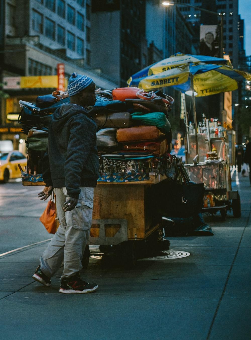 man standing beside brown stal at nighttime