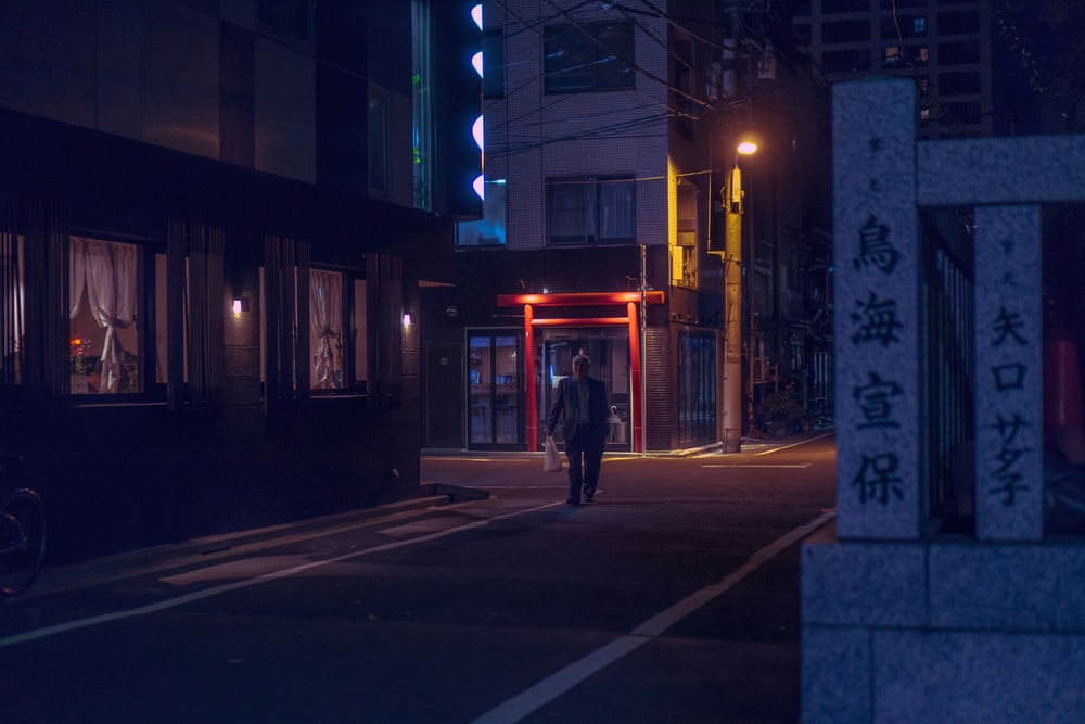 man walking in the road at nighttime