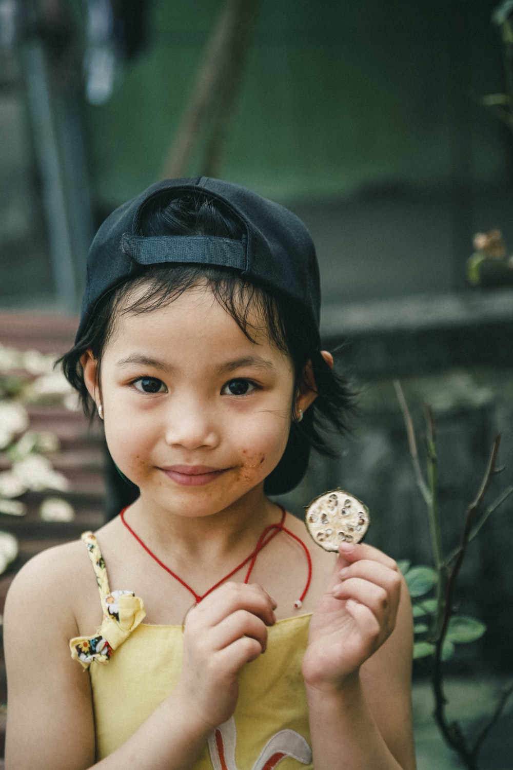 portrait photography of girl holding round coin