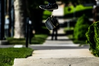 black skateboard floating in mid air at daytime