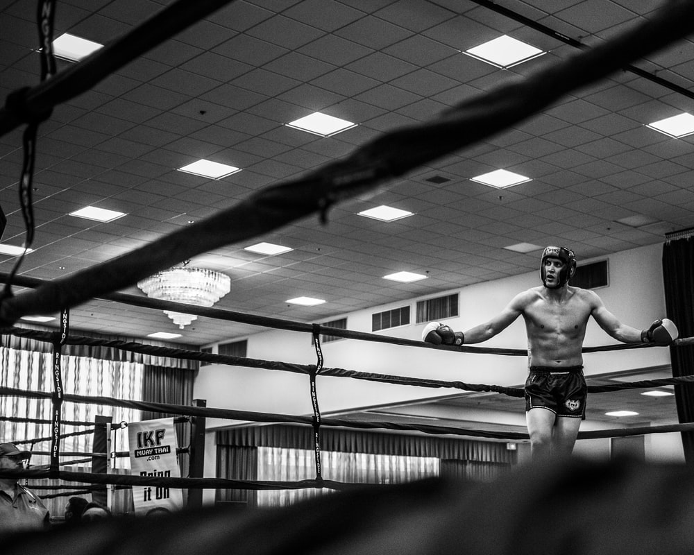 man leaning on boxing ring's pole