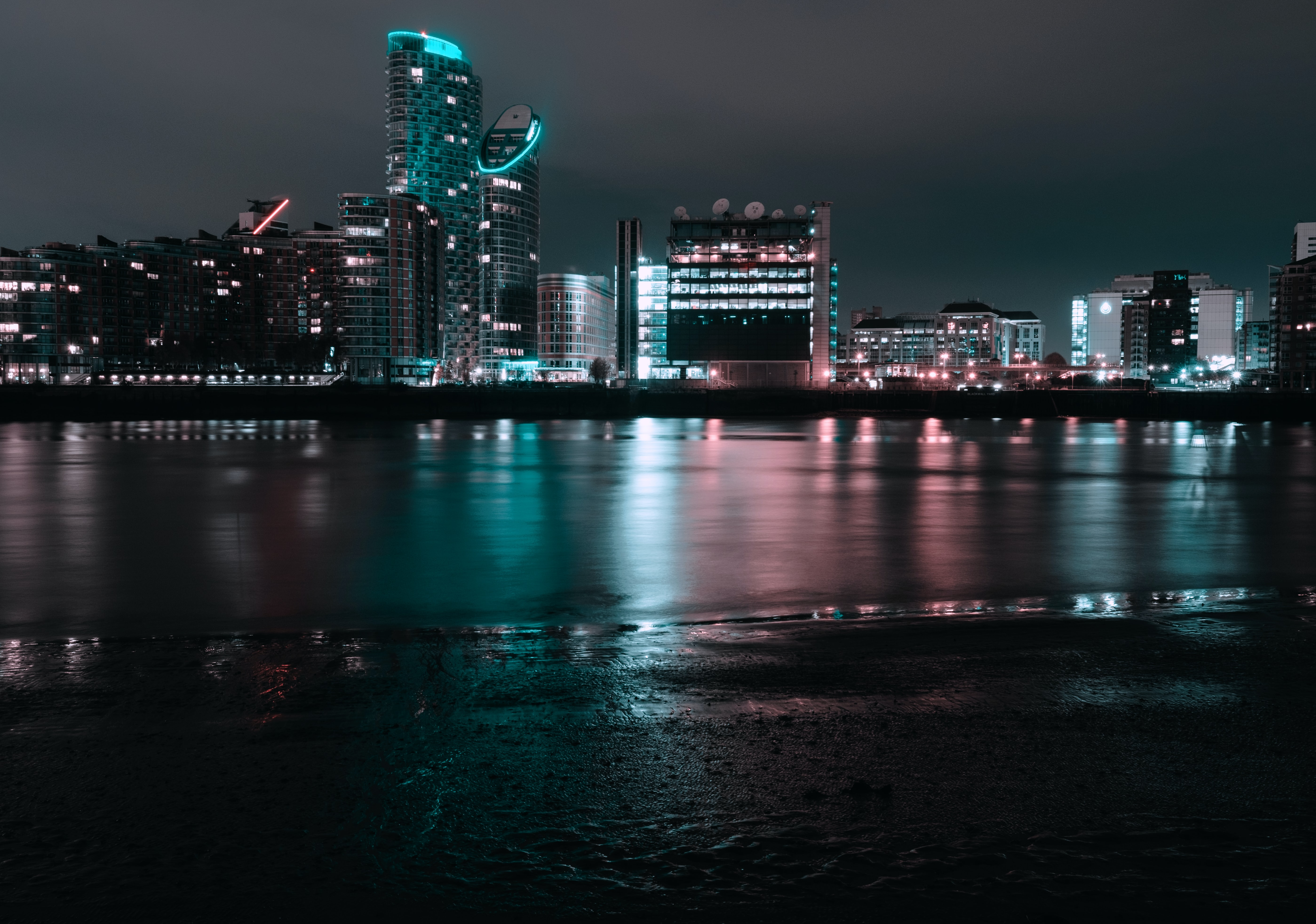 city near body of water during night