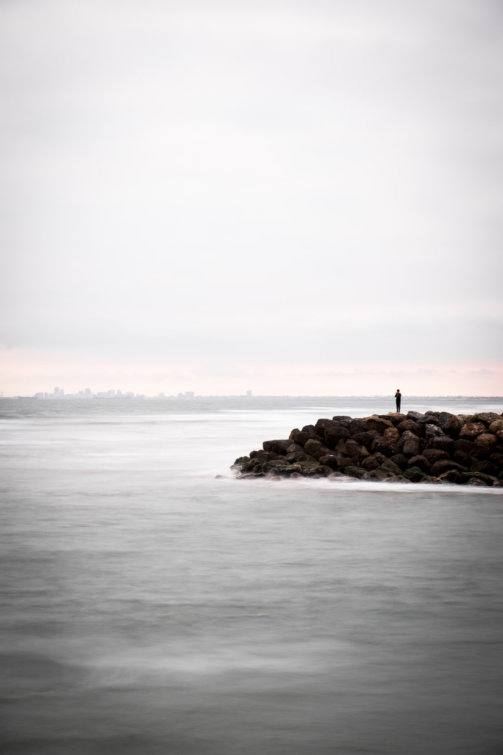 person standing on rocks surrounded by body of water