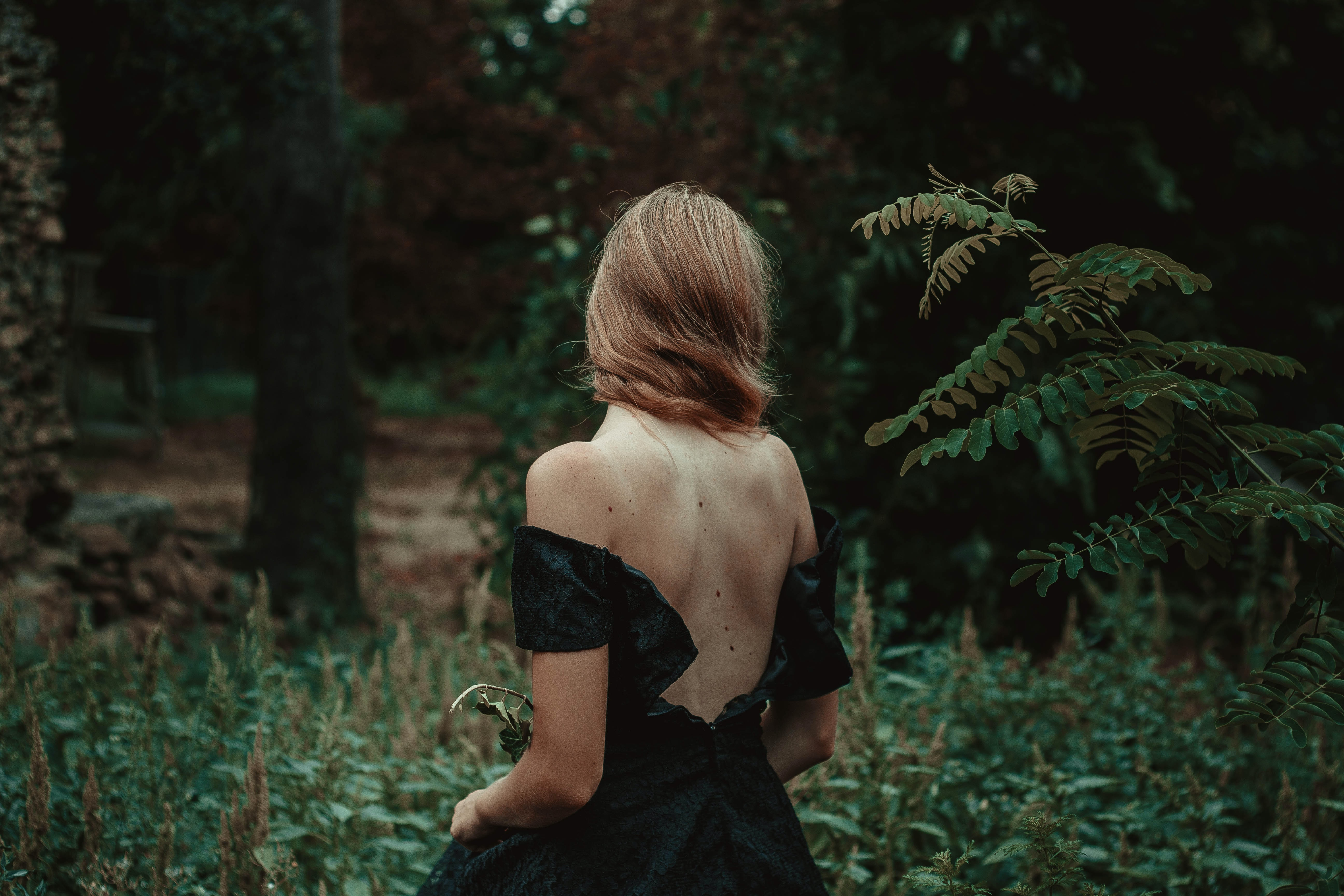 selective focus photography of woman standing on forest