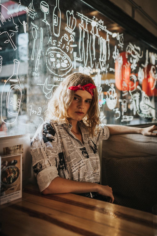 woman sitting behind graffiti glass wall