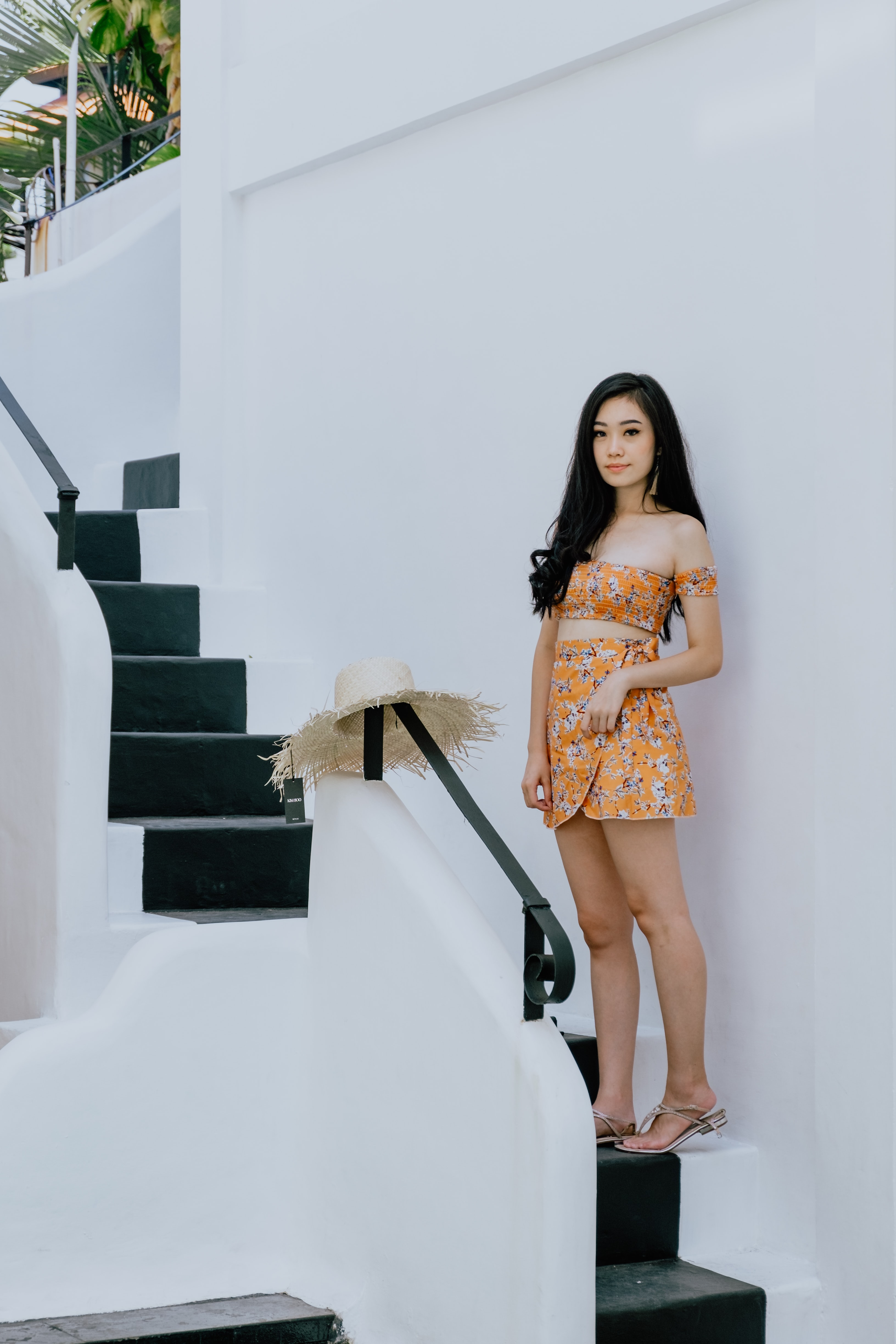 woman wearing orange floral tube top and skirt standing on stair beside wall