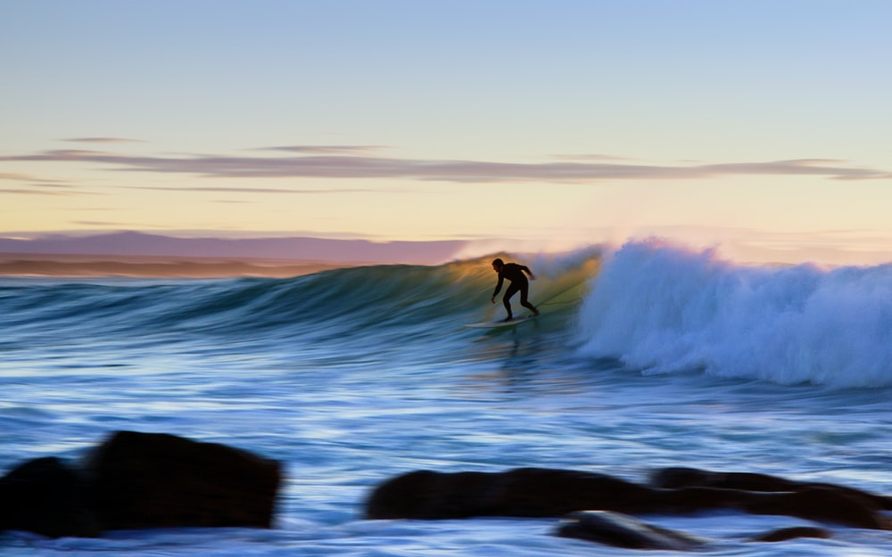 man surfing at the ocean during sunset