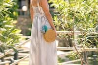 Woman with fashionable stylish rattan bag and silk