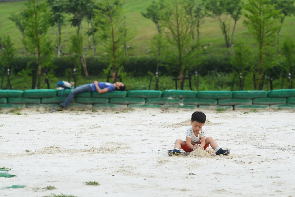 man lying on rail and boy playing with sand