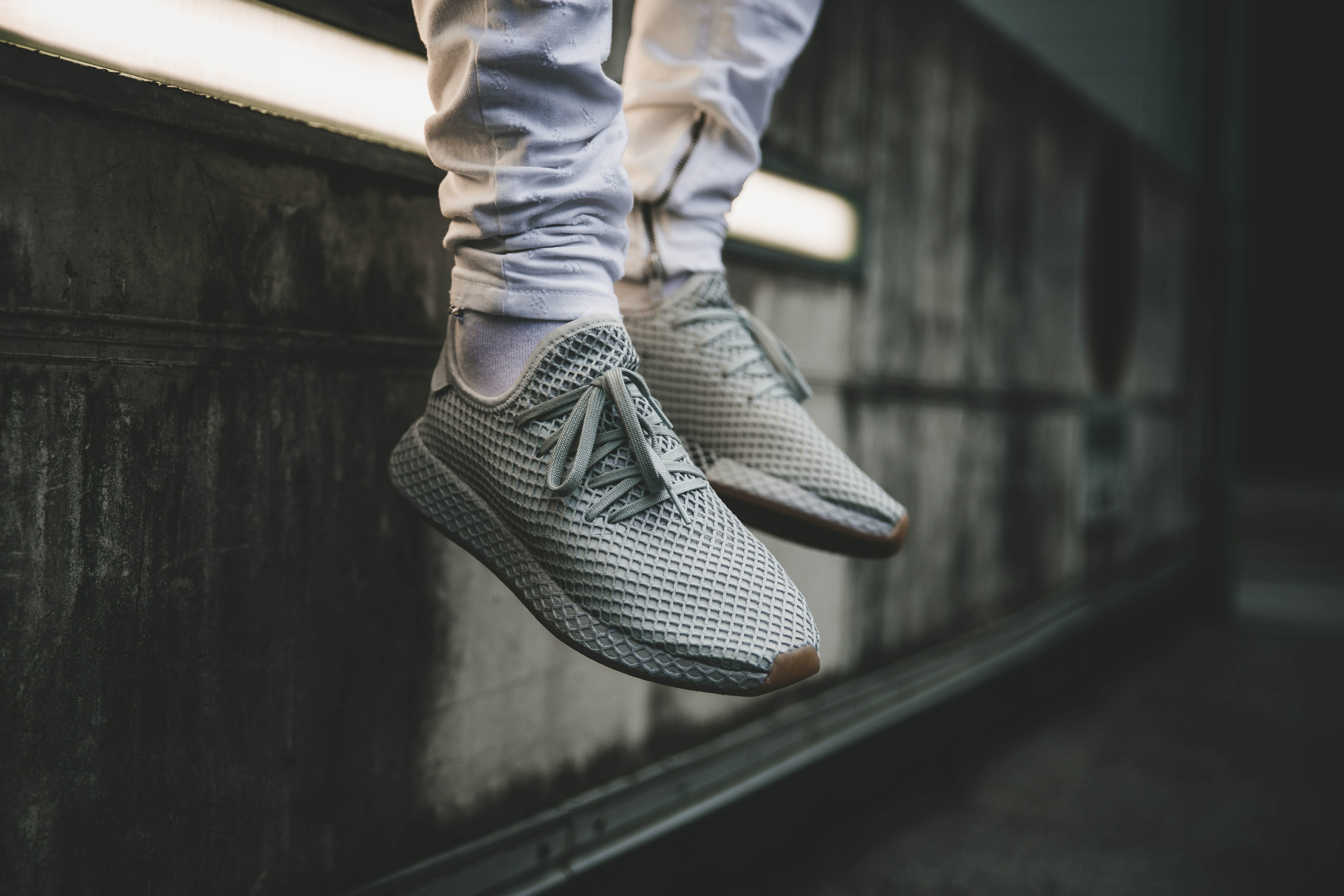 person wearing gray Adidas Boost sneakers