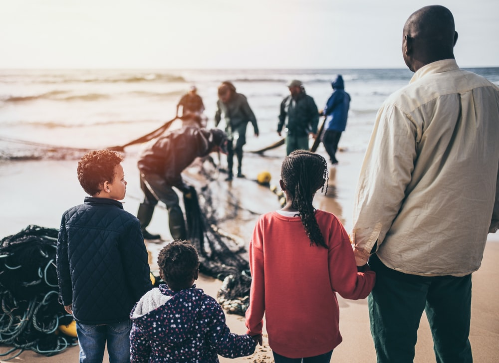 group of people standing on seashore