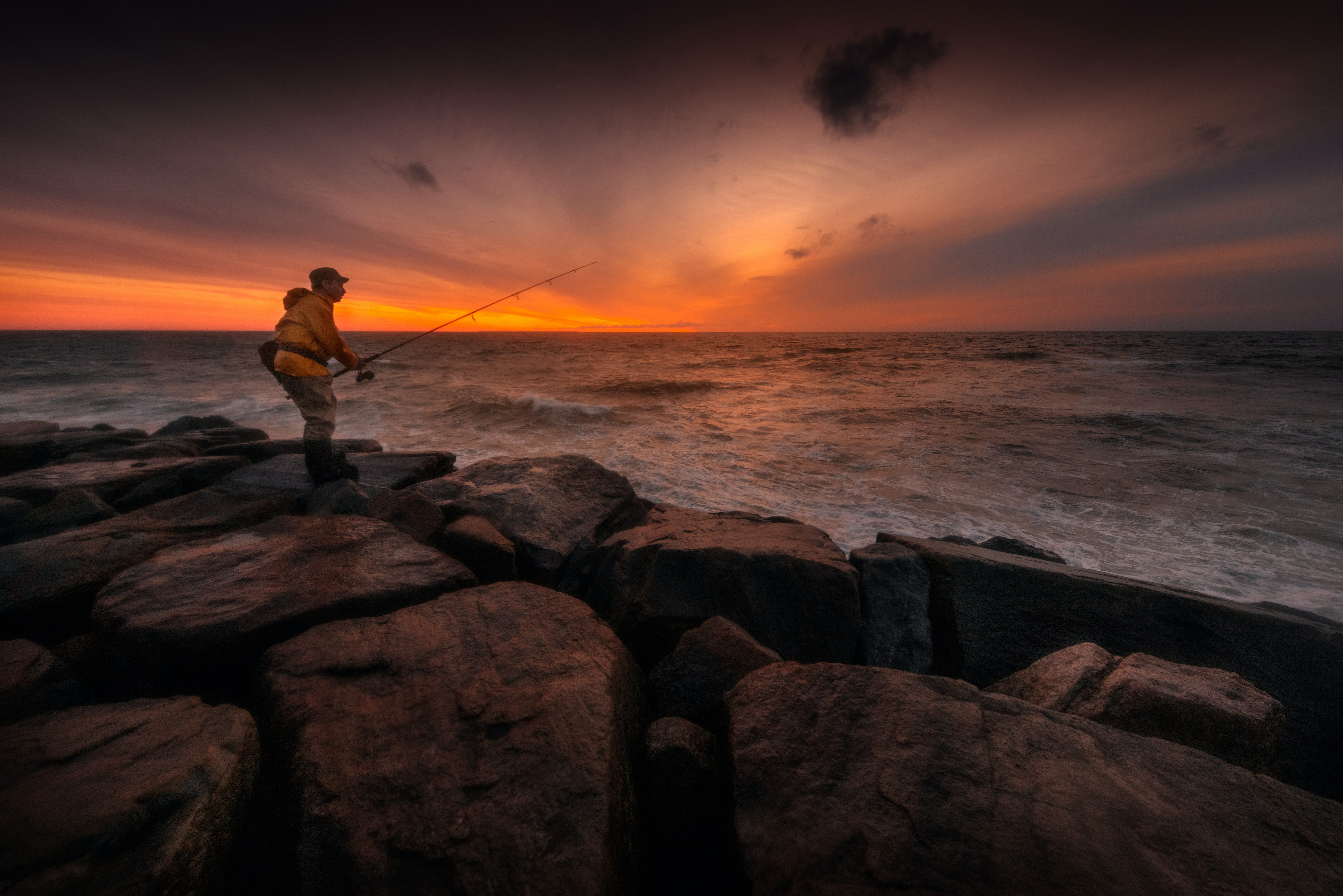 man standing on rock fishing on body of water during sunset