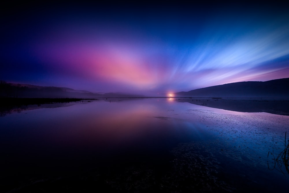 landscape photography of body of water under dramatic sky