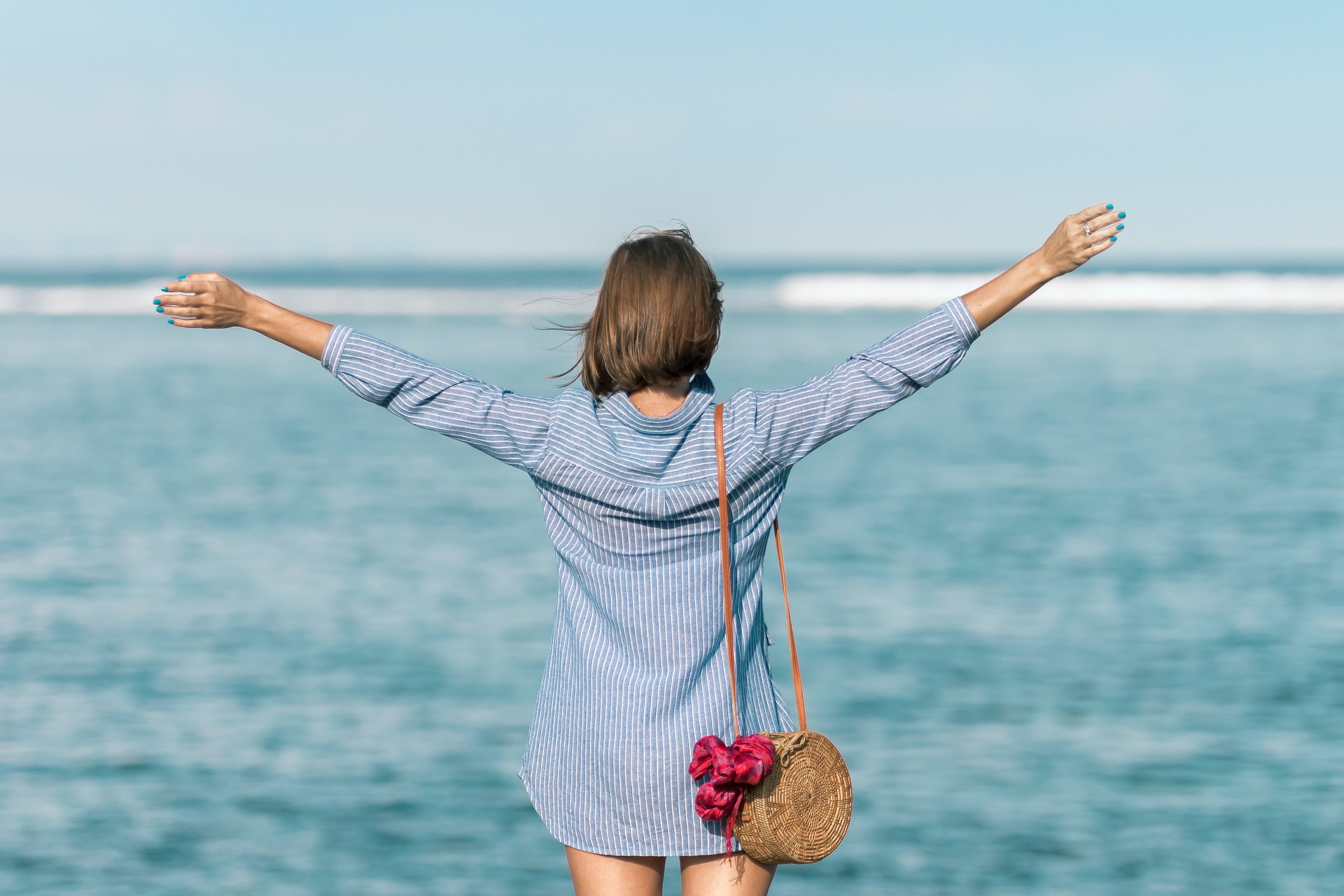 woman spreading hands standing near body of water