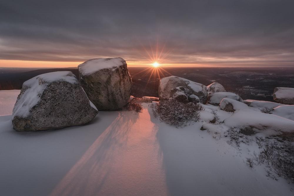 snow covered rocks against golden sun