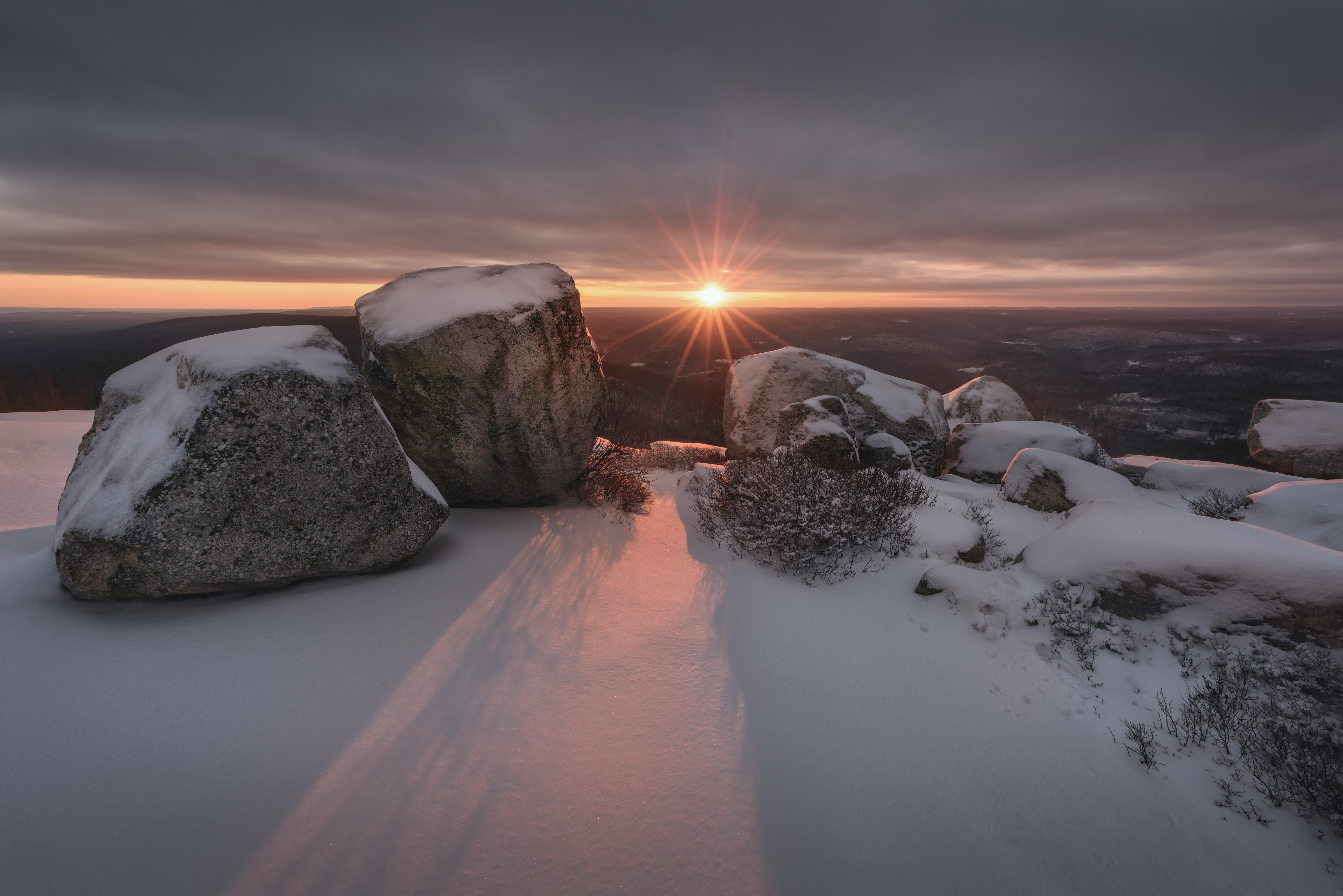 snow covered rocks against golden sun