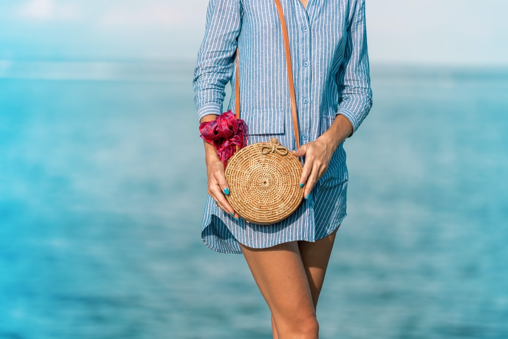 woman wearing blue and white striped dress shirt dress with brown wicker crossbody bag near sea at daytime