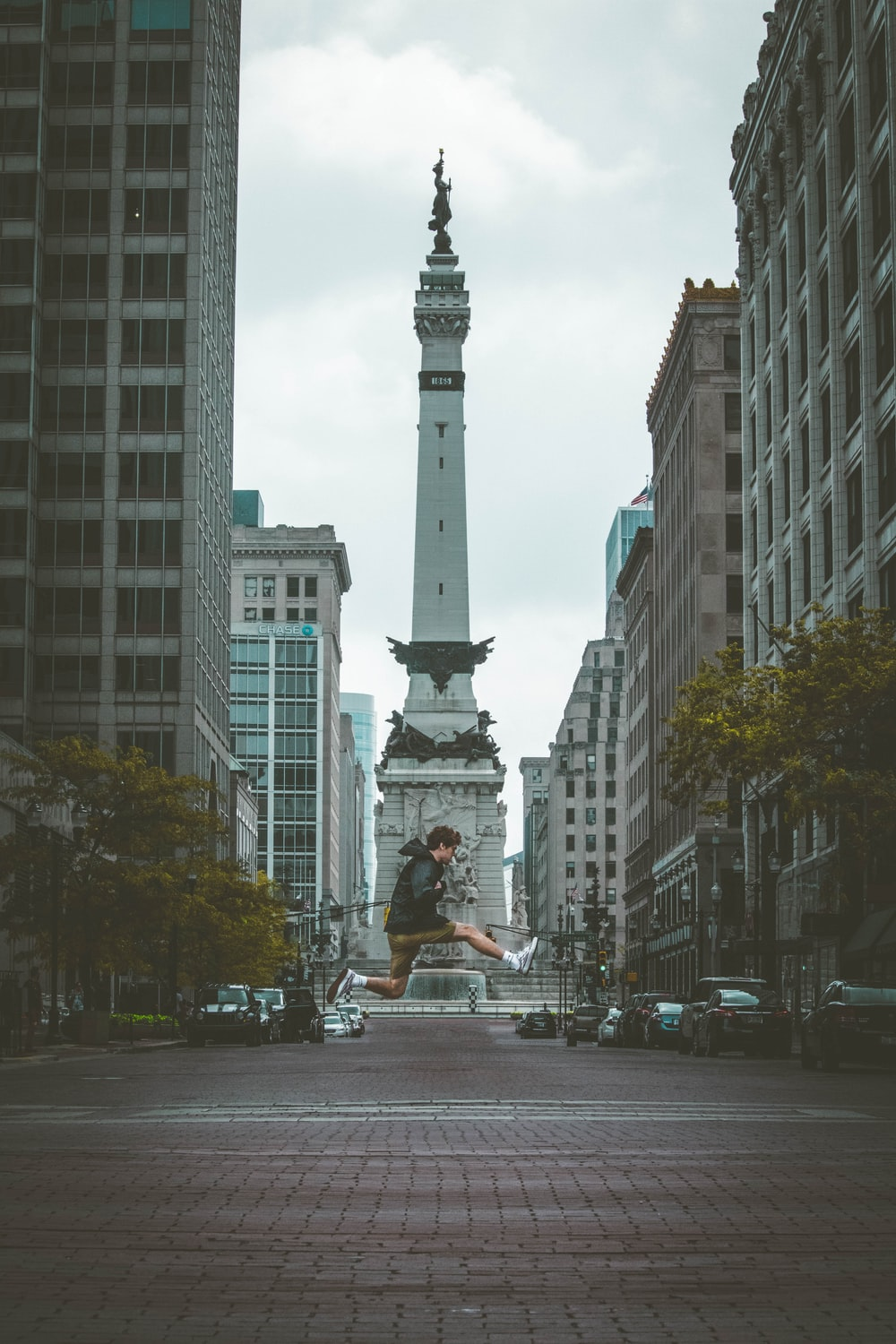 jump shot photo of man with monument background between buildings