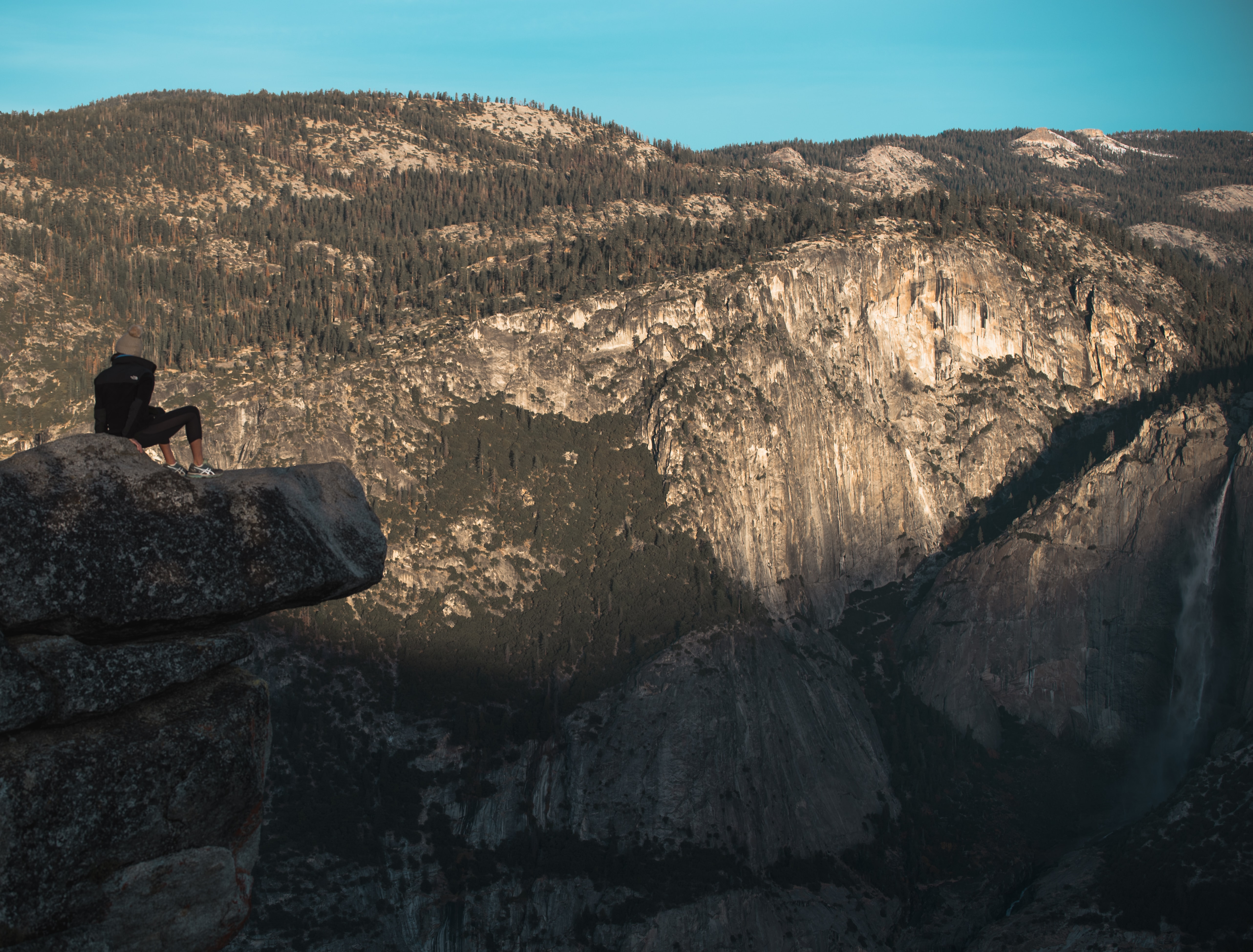 person sitting on cliff