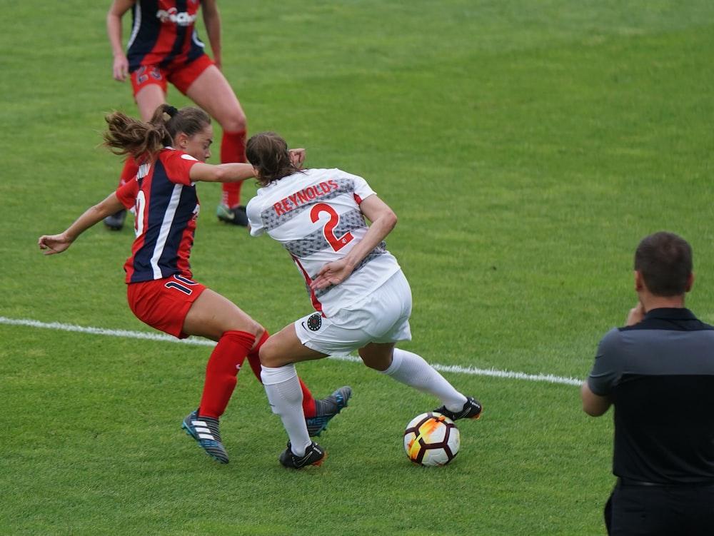 women playing soccer in an open field
