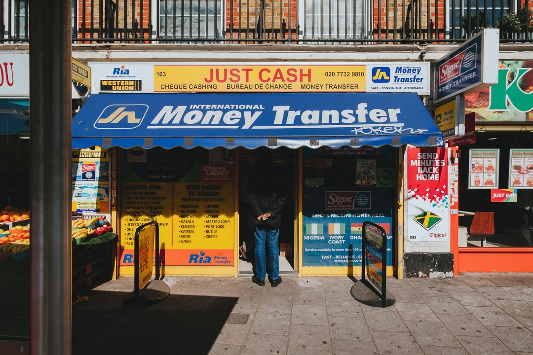 Street scene of a man waiting in line at a money transfer shop in London, notoriously dodgy places.