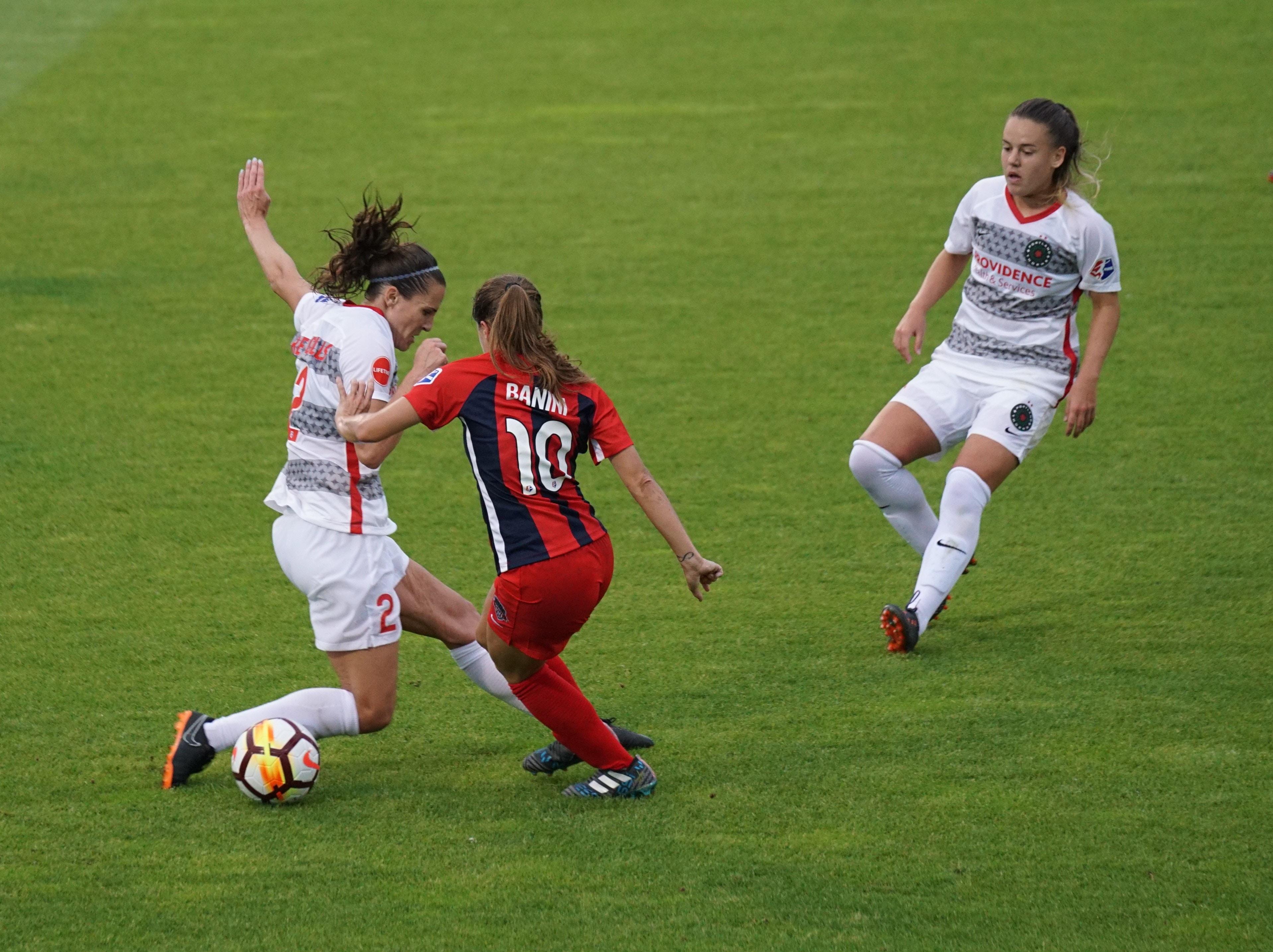 three women playing soccer