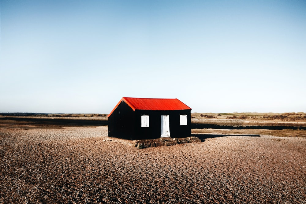 black and red wooden house in the middle of nowhere