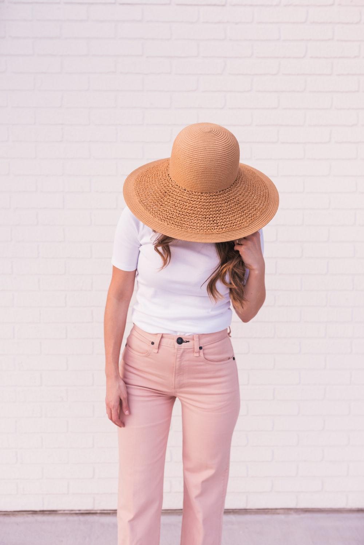 woman wearing white shirt, pink pants, and brown sun hat
