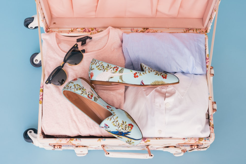 clothing items and pair of shoes in luggage