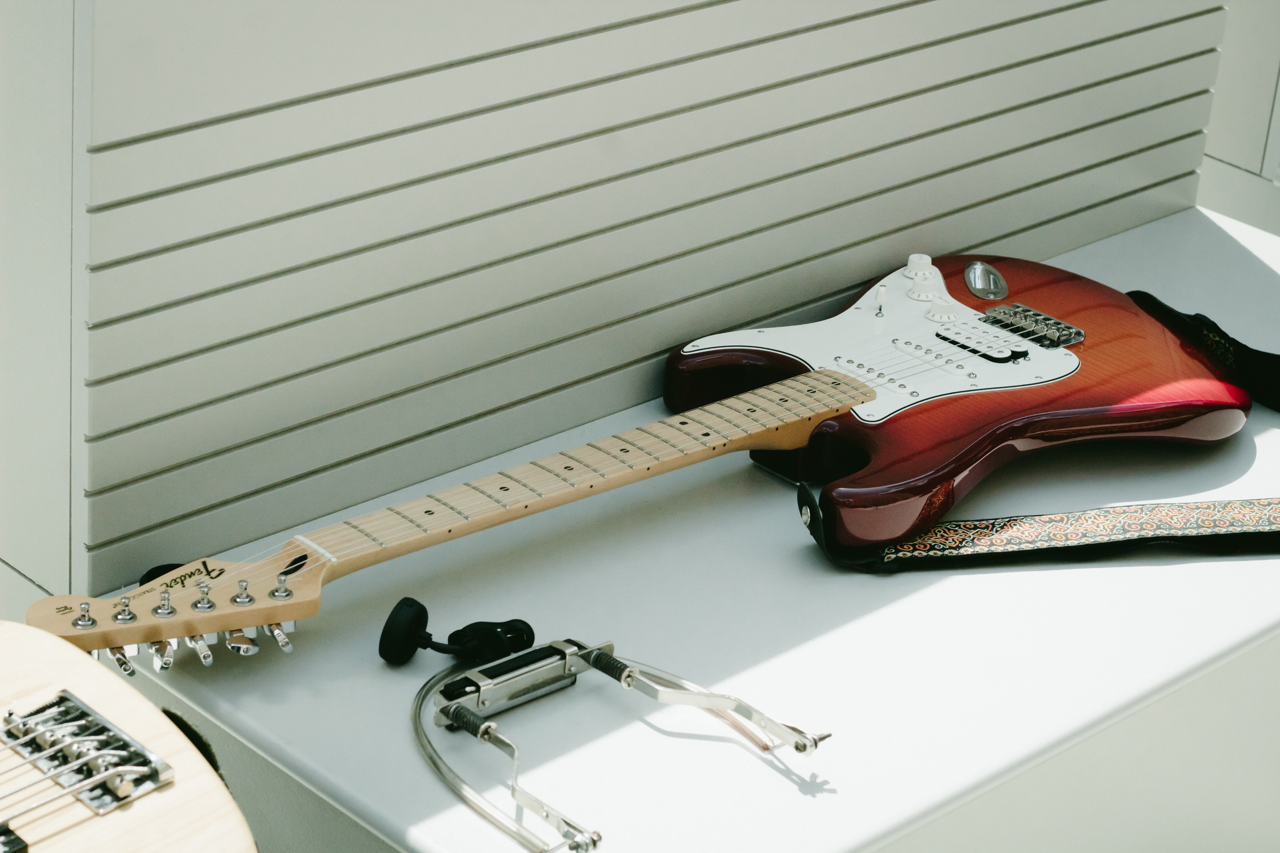 white and brown electric guitar on top of white wooden surface