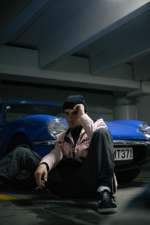 man sitting near blue car