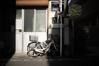 white bicycle parked beside white pole